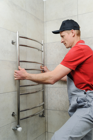 Plumber installs towel warmer on the wall in the bathroom.