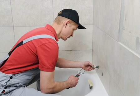Installing bath faucet. Plumber  installs eccentric with an adjustable wrench. Banco de Imagens