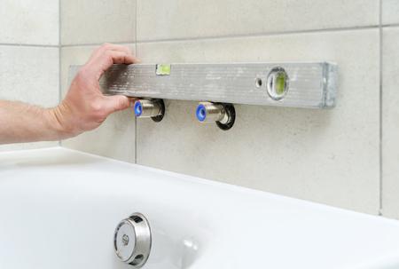 Plumber level checks for eccentrics bath faucet. Фото со стока