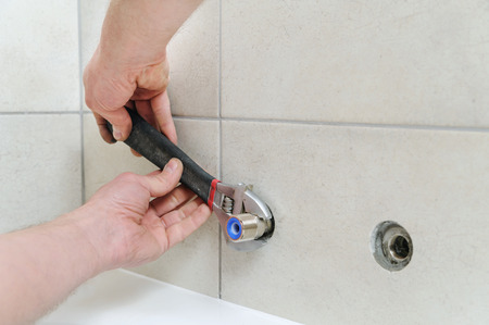 Installing bath faucet. Plumber  installs eccentric with an adjustable wrench. Фото со стока