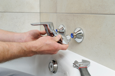 Plumber holding a bath  faucet and installs it.