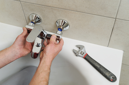 Plumber fixing bath faucet with an adjustable wrench. Фото со стока