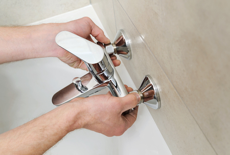 Plumber holding a bath tub faucet and installs it.