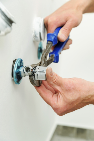 Plumber installs angel valve using pliers wrench.