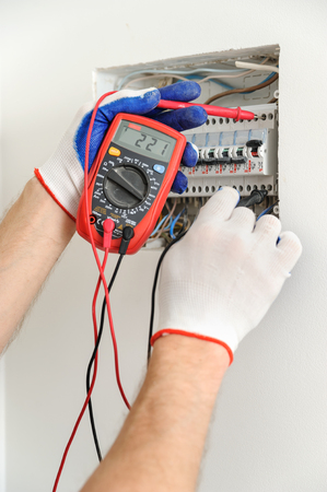 Electrician check voltage in electrical fuse box with a multimeter.
