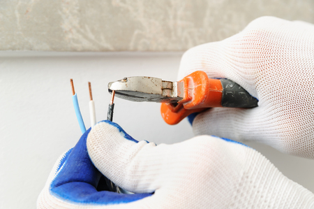 Electrican shortens electric wire using wire cutters.