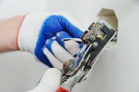 Electric stripping insulation from wire for installation an electrical outlet. Фото со стока