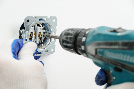 Electrician installs electrical outlet using a screwdriver.