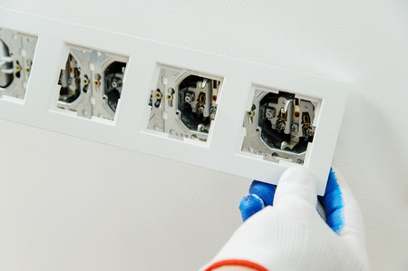 Electrician installs decorative frame on electric  sockets.