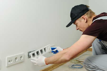Electrician installs decorative frame on electric and TV sockets. Banco de Imagens