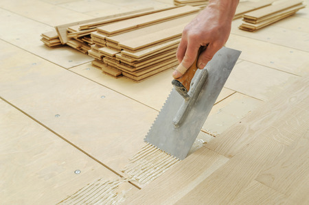 Laying hardwood parquet. Worker puts glue on the floor.