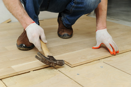 Laying hardwood parquet. Worker clamps parquet with a hammer.