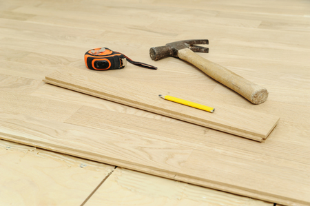 Laying hardwood parquet. Hammer, pencil, measuring tape or flooring. Фото со стока