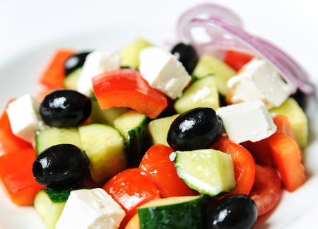Greek salad closeup. The mixture of the vegetables: pepper, cucumber, onion, olives and cheese.