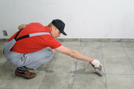 Grouting ceramic tiles. Tilers filling the space between tiles using a rubber trowel. Фото со стока