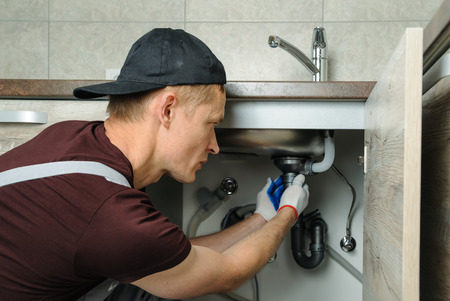 Worker sets trap for kitchen sink. Stock Photo