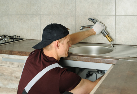 Worker installs faucet for kitchen sink.