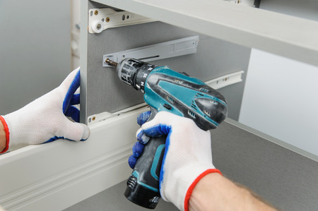 Installation of kitchen. Workman fixes the drawer in cabinet. Stock Photo