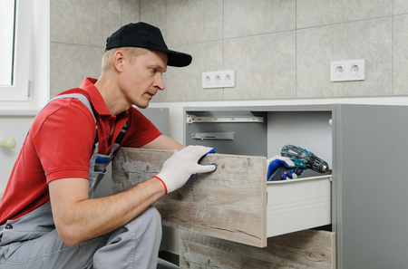 Installation of kitchen. Workman fixes the drawer in cabinet. Фото со стока