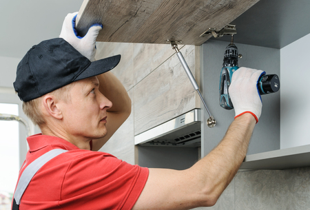 Installation of kitchen. Workman fixes  a hinge to a kitchen cabinet. Фото со стока