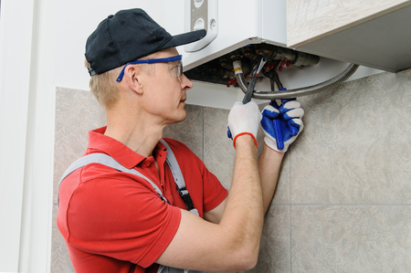 Plumber attaches to pipe gas boiler using adjustable wrench. Stock Photo