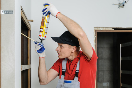 Installing door unit. Workman fixing the door frame using a mounting foam.