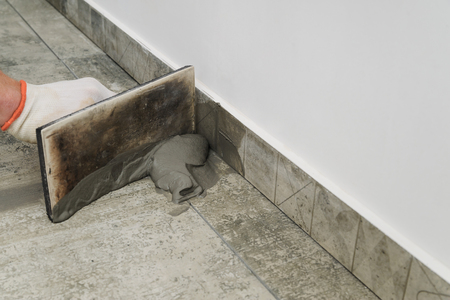Grouting ceramic tiles. Tilers filling the space between tiles using a rubber trowel. Standard-Bild