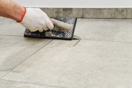 Grouting ceramic tiles. Tilers filling the space between tiles using a rubber trowel. 写真素材