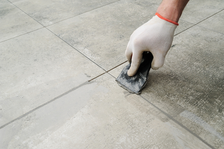 Grouting ceramic tiles. Tilers filling the space between tiles using a rubber trowel. Stock Photo