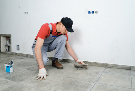 Grouting ceramic tiles. Tilers filling the space between tiles using a rubber trowel. Banco de Imagens