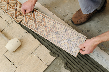 Worker putting tiles on the floor. It installs strips.