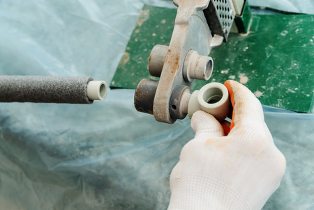 Soldering plastic pipe. A worker heats the pipe and knee for future connections using electrosoldering.