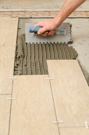 Worker installs tiles on the floor. He put glue using comb trowel.