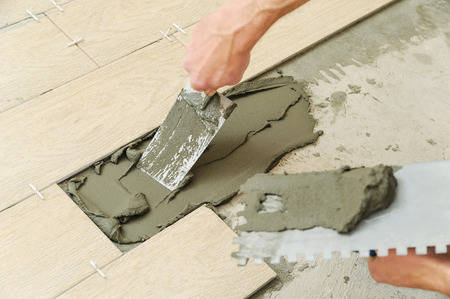 Worker installs tiles on the floor. He put adhesive using a trowel.