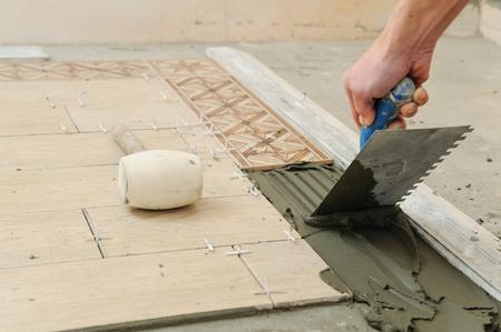 Worker instalis tiles on the floor. He put glue using comb trowel.