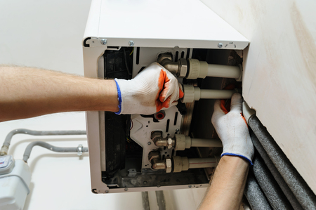 Installation of home heating. A worker attaches the pipe to the gas boiler. Stock Photo