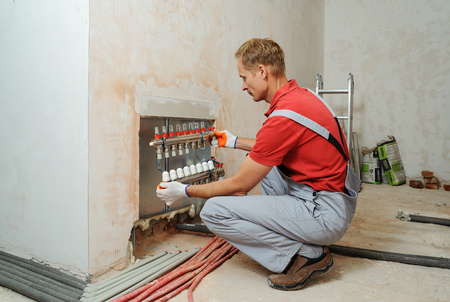 Installation of home heating. A worker holds the underfloor heating manifold.