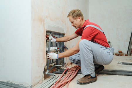 Installation of home heating. A worker attaches the tube to the collector heating. Stock Photo