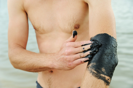 Man applies black therapeutic mud on his elbow.