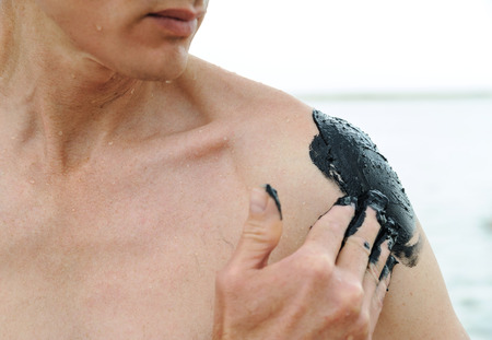 Man applies black therapeutic mud on his shoulder.