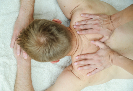 Health massage therapy. Female hands are massaging the back of a man.
