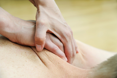 Health massage therapy. Female hands are massaging the shoulder of a man. Фото со стока