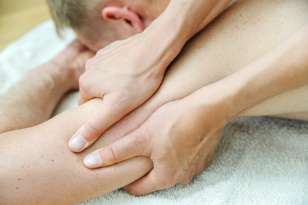 Health massage therapy. Female hands are massaging the mans arm. Stock Photo