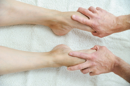 Massage of feet and legs. Male hands are massaging female feet.