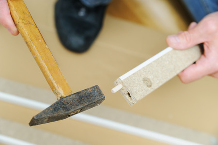 A man is hammering a wooden pin into a furniture board.