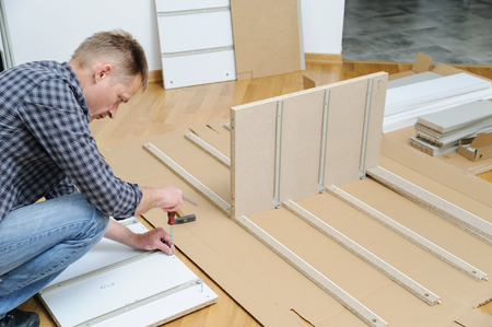 The man is installing Joint Connector Bolts in the furniture board. Banque d'images