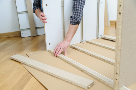 A man is assembling furniture from chipboard boards.