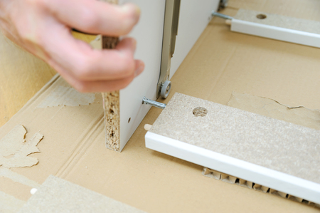 The man is assembling furniture from chipboard boards. Фото со стока