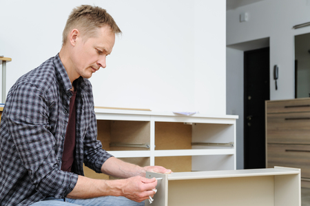 Mounting the chest of drawers. The man is joining the pieces of the drawer. Фото со стока