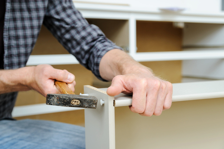 Mounting the chest of drawers. A  man is using a hammer to fix the drawers boards. Фото со стока